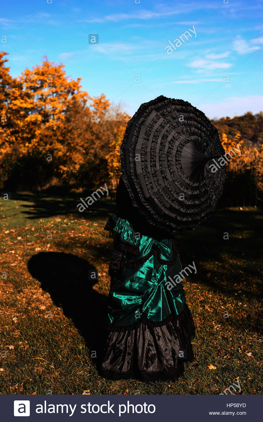 Rückansicht des viktorianischen Frau mit Regenschirm Stockfoto