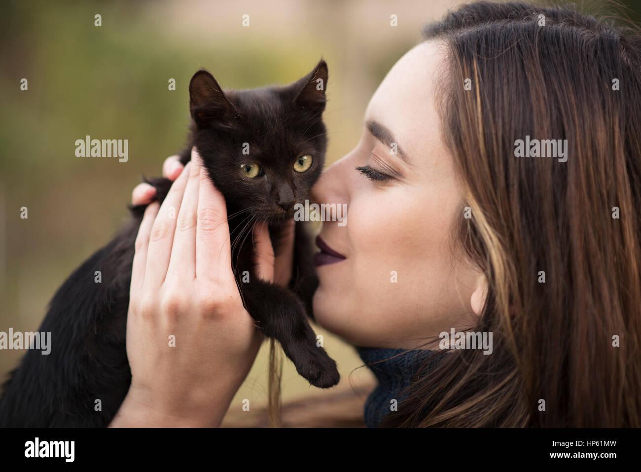 Junge hübsche Frau Kuscheln mit einer schwarzen Katze Stockbild
