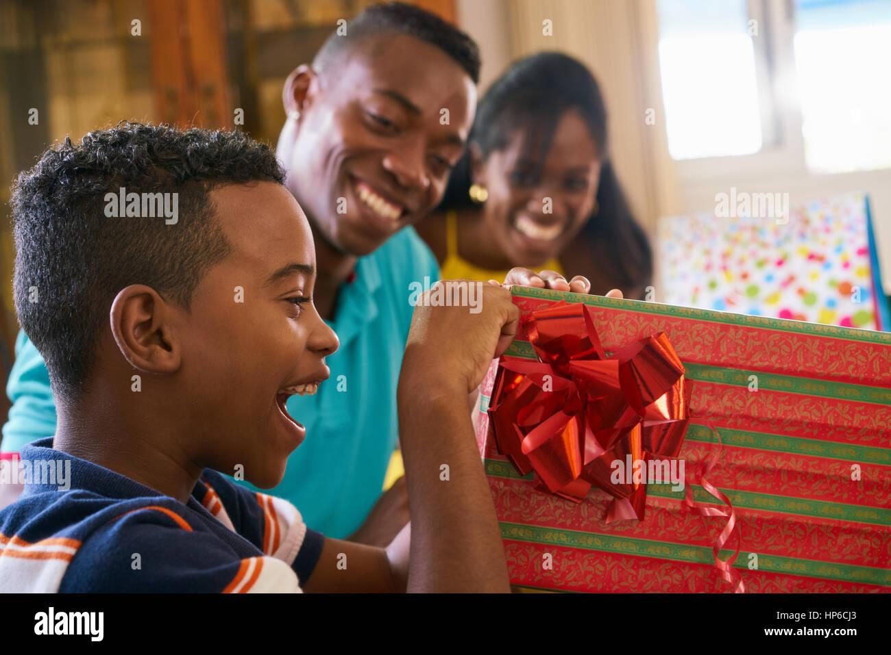 Glückliche schwarze Familie zu Hause. African american Vater, Mutter und Kind feiert Geburtstag, Spaß Stockbild
