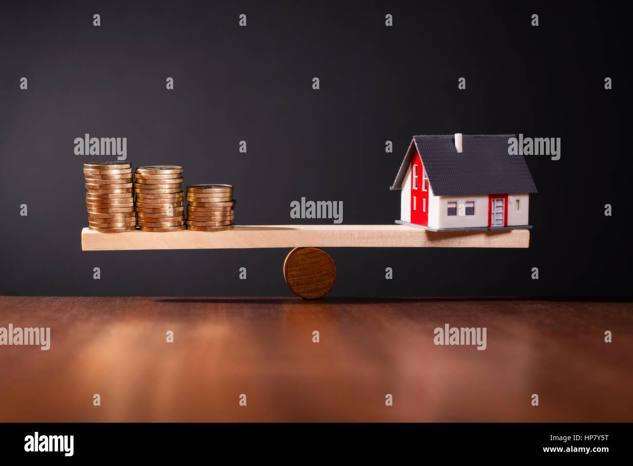 Wippe mit einem Haus auf der einen Seite und Stapel von Münzen auf der anderen Seite. Stockbild