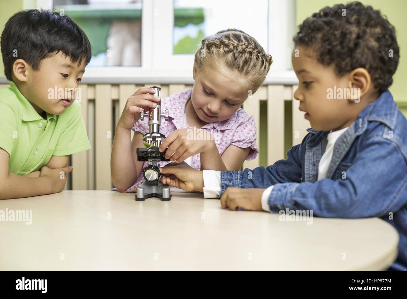 Drei kinder experimentieren mit einem mikroskop model release