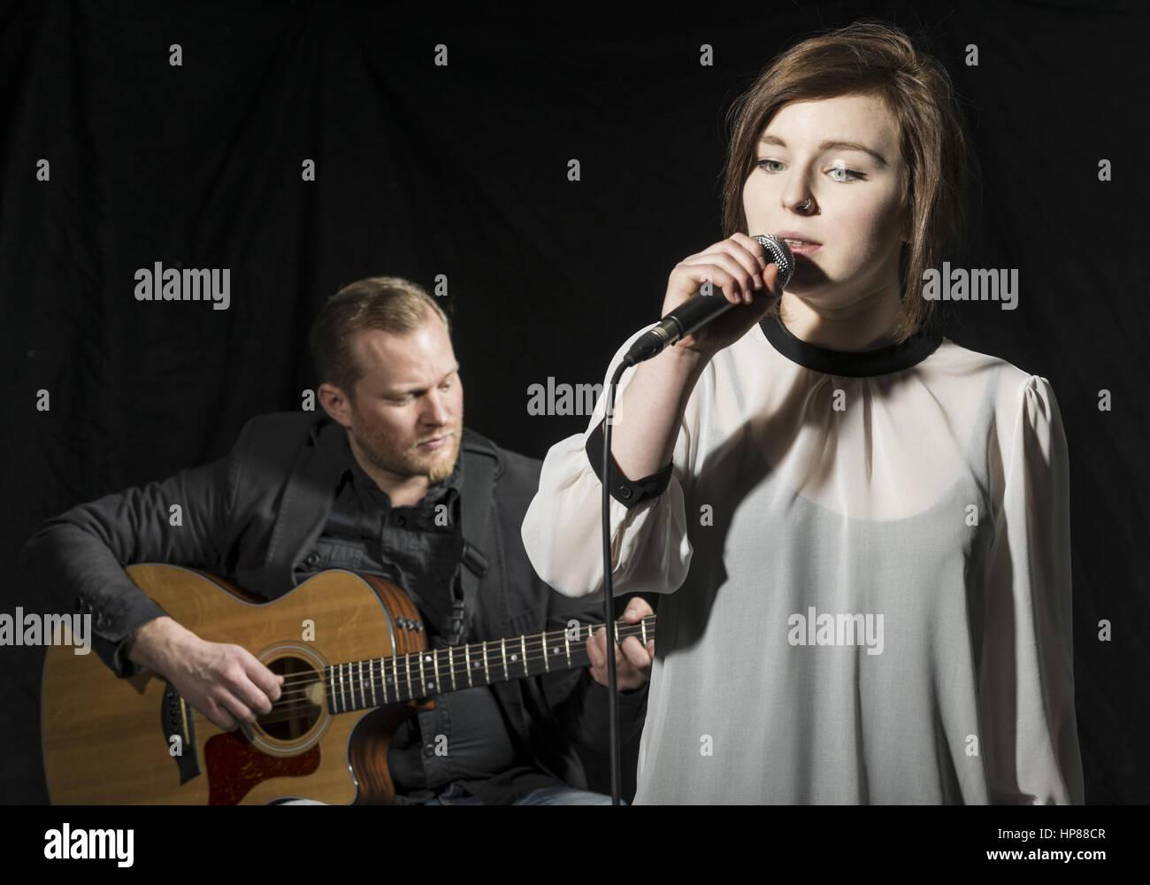 Musiker Mit Gitarre, Saengerin Mit Mikrofon (Model-Release) Stockbild