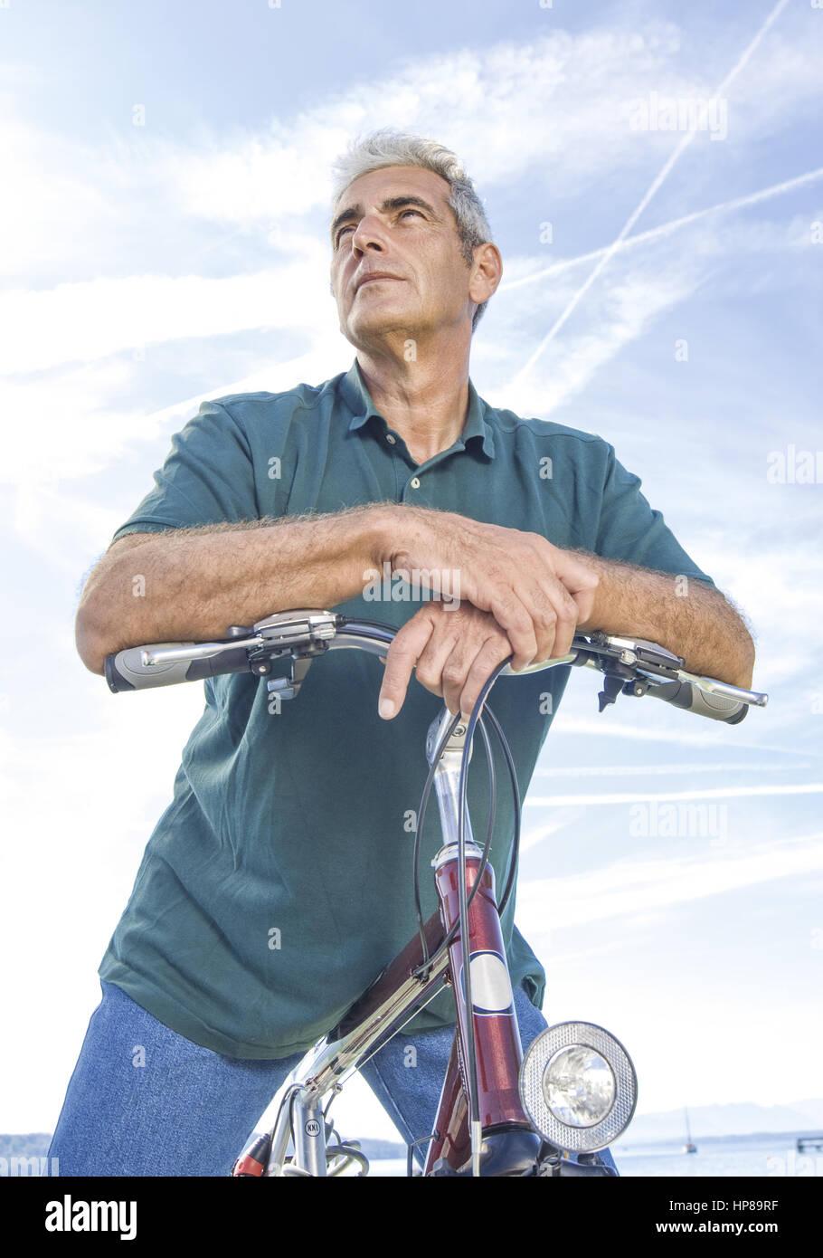 Senior Auf Fahrrad, Gegen Himmel (Model-Release) Stockbild