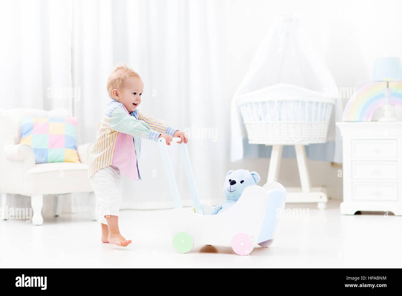 Baby Boy Mit Hölzernen Push Walker In Weiße Schlafzimmer Mit Pastell  Regenbogen Farbe Spielzeug Laufen Lernen. Spielzeug Für Die Ersten Schritte  Des Kindes ...