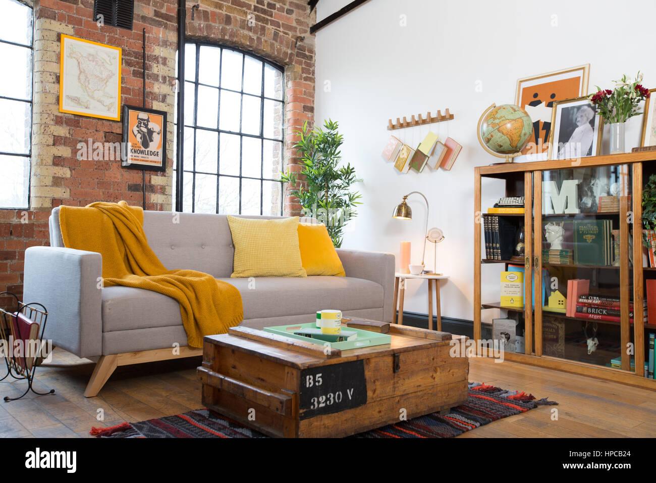ein wohnzimmer mit backsteinw nden und eine graue danish design sofa mit gelben decke und kissen. Black Bedroom Furniture Sets. Home Design Ideas