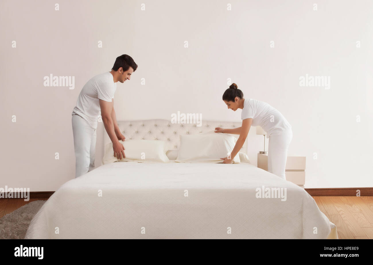 Paar Bett im Schlafzimmer machen Stockfoto