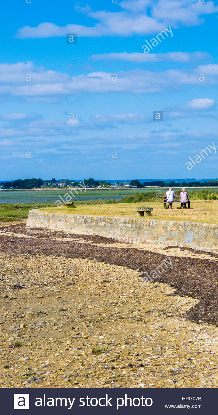 Frankreich, Bretagne (Bretagne), Departement Morbihan, Golfe du Morbihan. Zwei Menschen sitzen an einem Picknicktisch. Stockbild