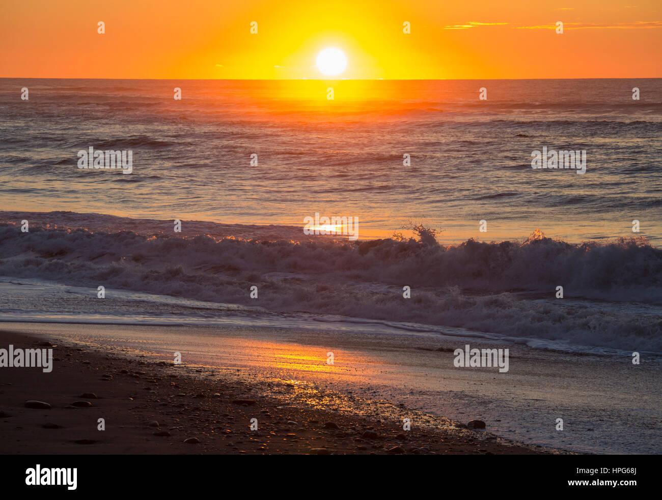 Okarito, Westland Tai Poutini Nationalpark, West Coast, New Zealand. Goldener Sonnenuntergang über der Tasmansee. Stockfoto