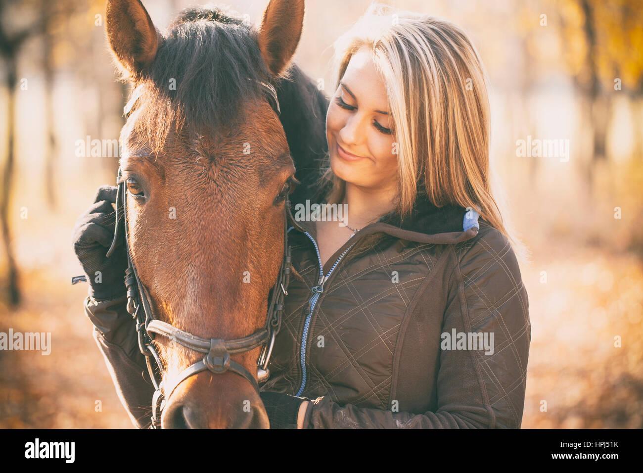 Frau mit Pferd im Sonnenuntergang Stockbild