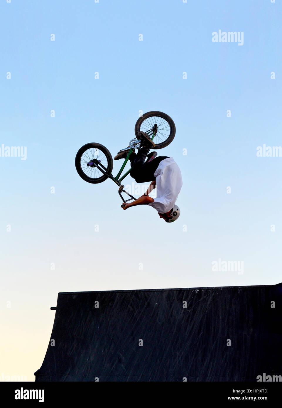 Eine Person, die ein Back flip über eine Fahrrad-Jump-Ramp auf einem BMX-Fahrrad Stockbild