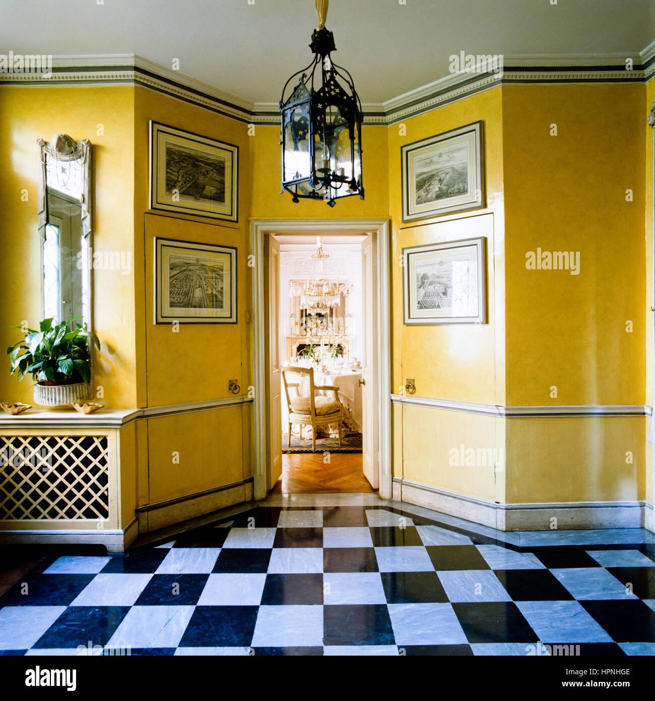 Ein Flur mit gelben Wänden und karierten Bodenbelag. Stockbild