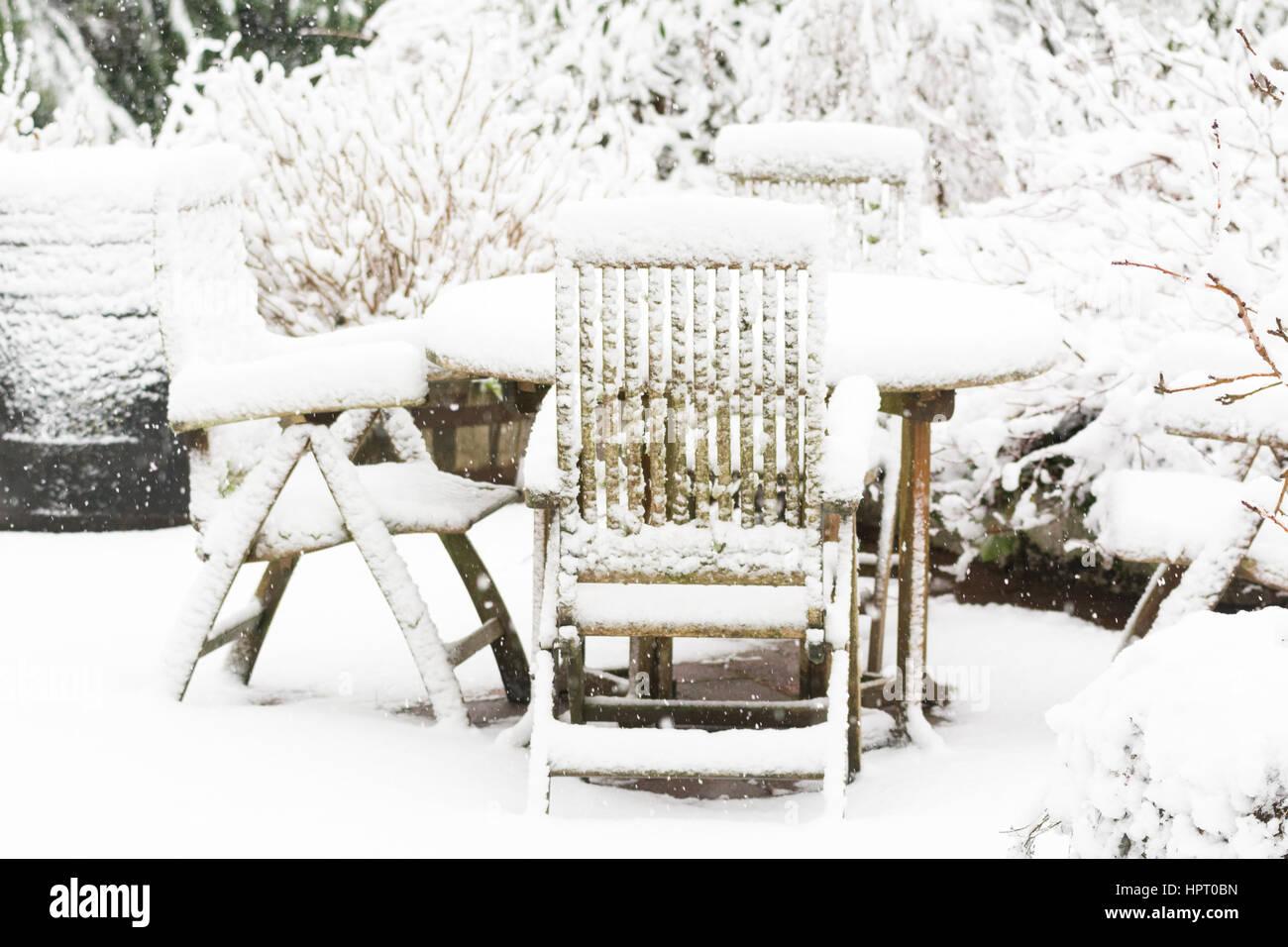 Garten im Schnee - Gartenmöbel, Tisch und Stühle im tiefen Schnee bedeckt Stockbild