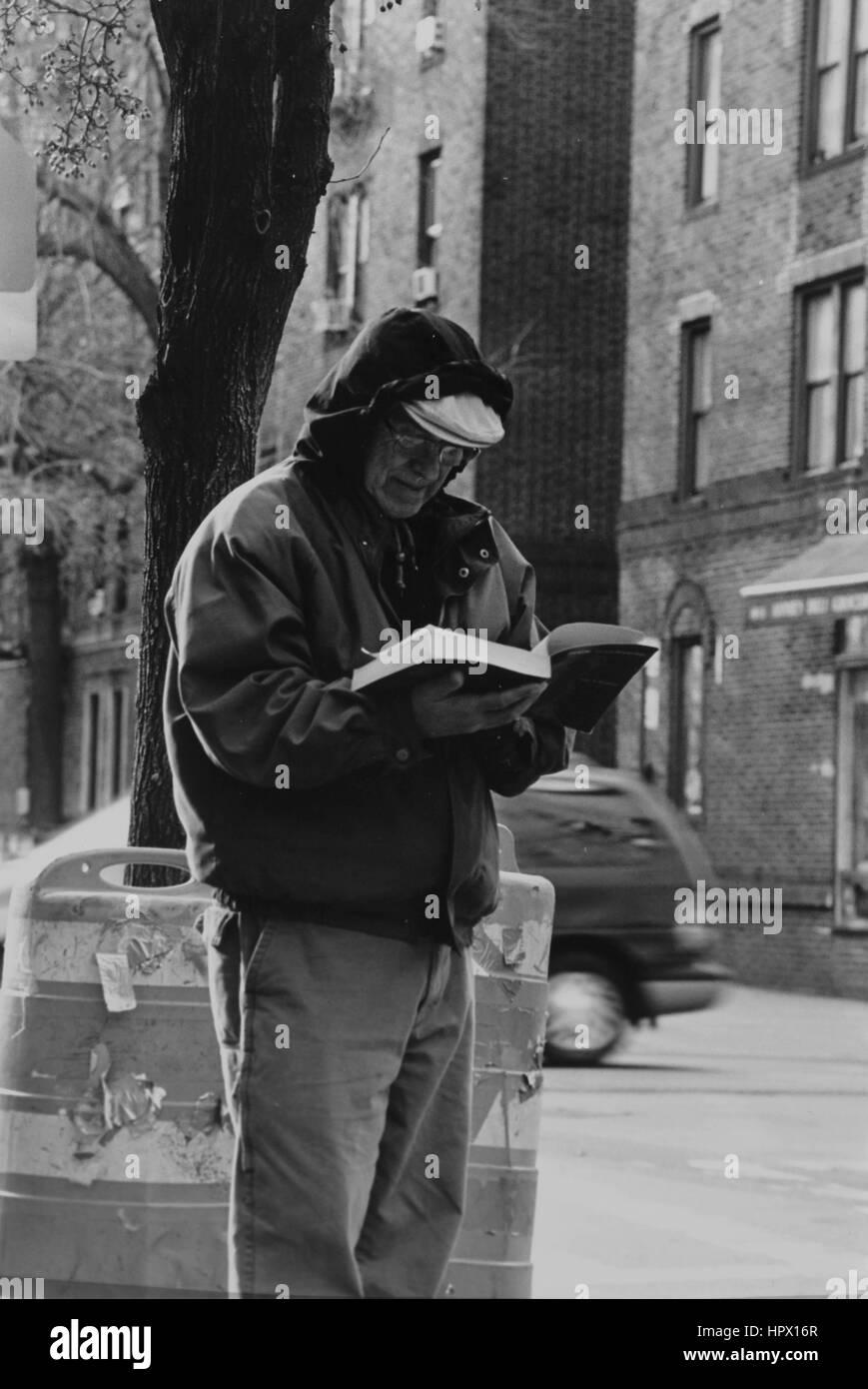 Ein Mann liest ein Buch in Jackson Heights Stockbild
