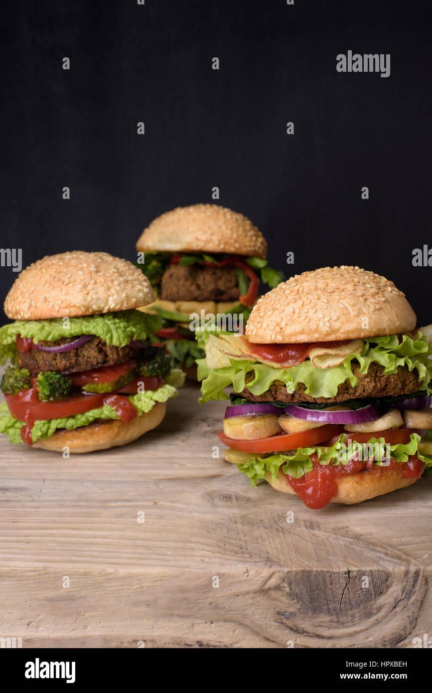 Saftige Hamburger auf Sesam Brötchen saftiges Rindfleisch-Burger mit frischem Salatzutaten auf einem rustikalen Stockbild