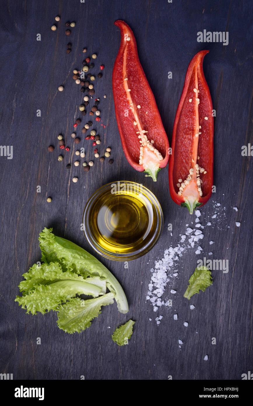 Salatzutaten: Paprika, Salat, Olivenöl auf rustikalen hölzernen Hintergrund. Frisches Gemüse, Ansicht Stockbild