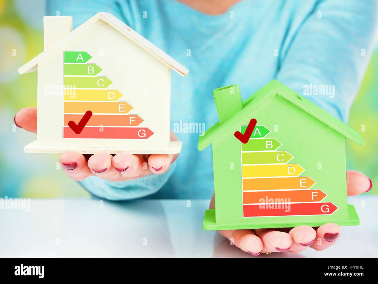 Konzept-Vergleich zwischen normalen und niedrigen Verbrauch Haus mit Energieeffizienzklasse Stockbild