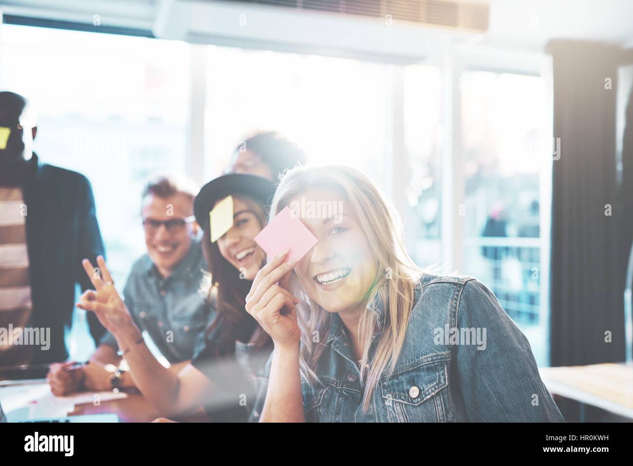 Schöne junge Menschen spielen Namensspiel, zwei Frauen und Männer posieren, Kamera gegen hellen Fenster Stockbild