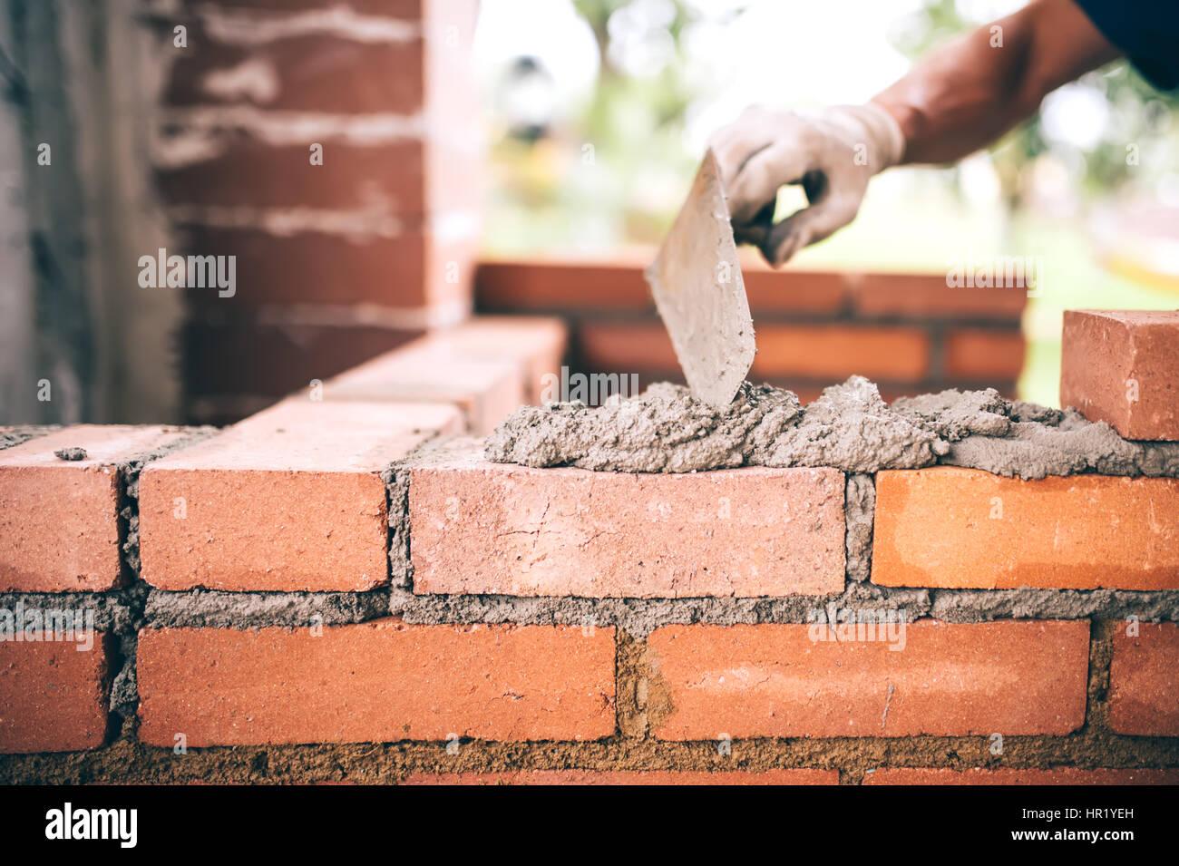 industrielle bauarbeiter maurer mauern bauen mit ziegel, mörtel und