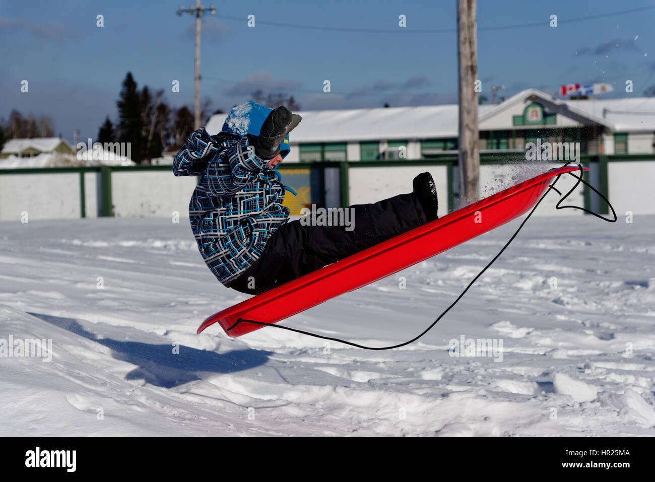 Ein kleiner Junge (4 Jahre alt) in die Luft sprang auf einem Schlitten in Quebec winter Stockbild