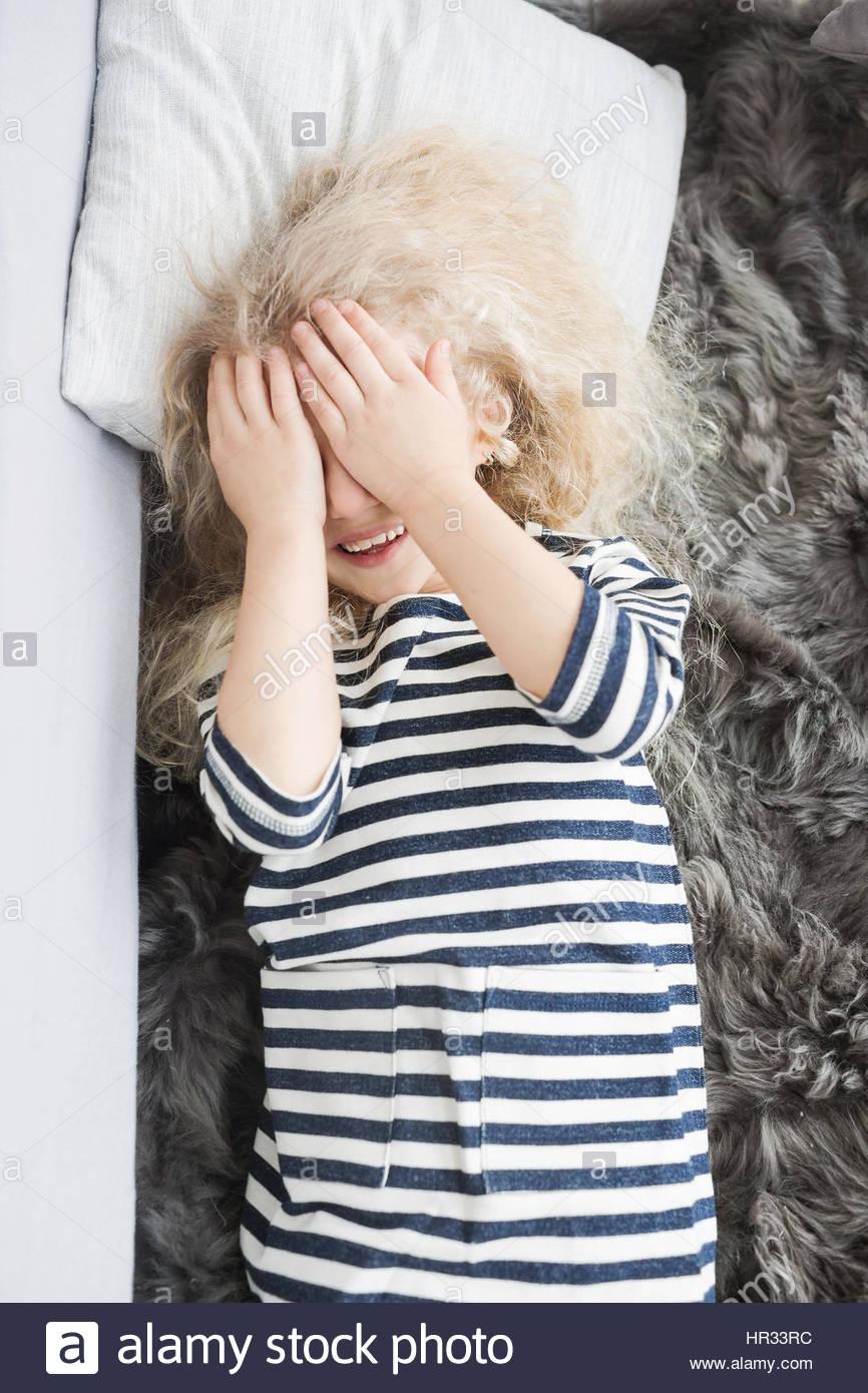 Kleines Mädchen mit weißem lockiges Haar in einem gestreiften vestin Bett.  Kleines Mädchen Spaß. Stockbild