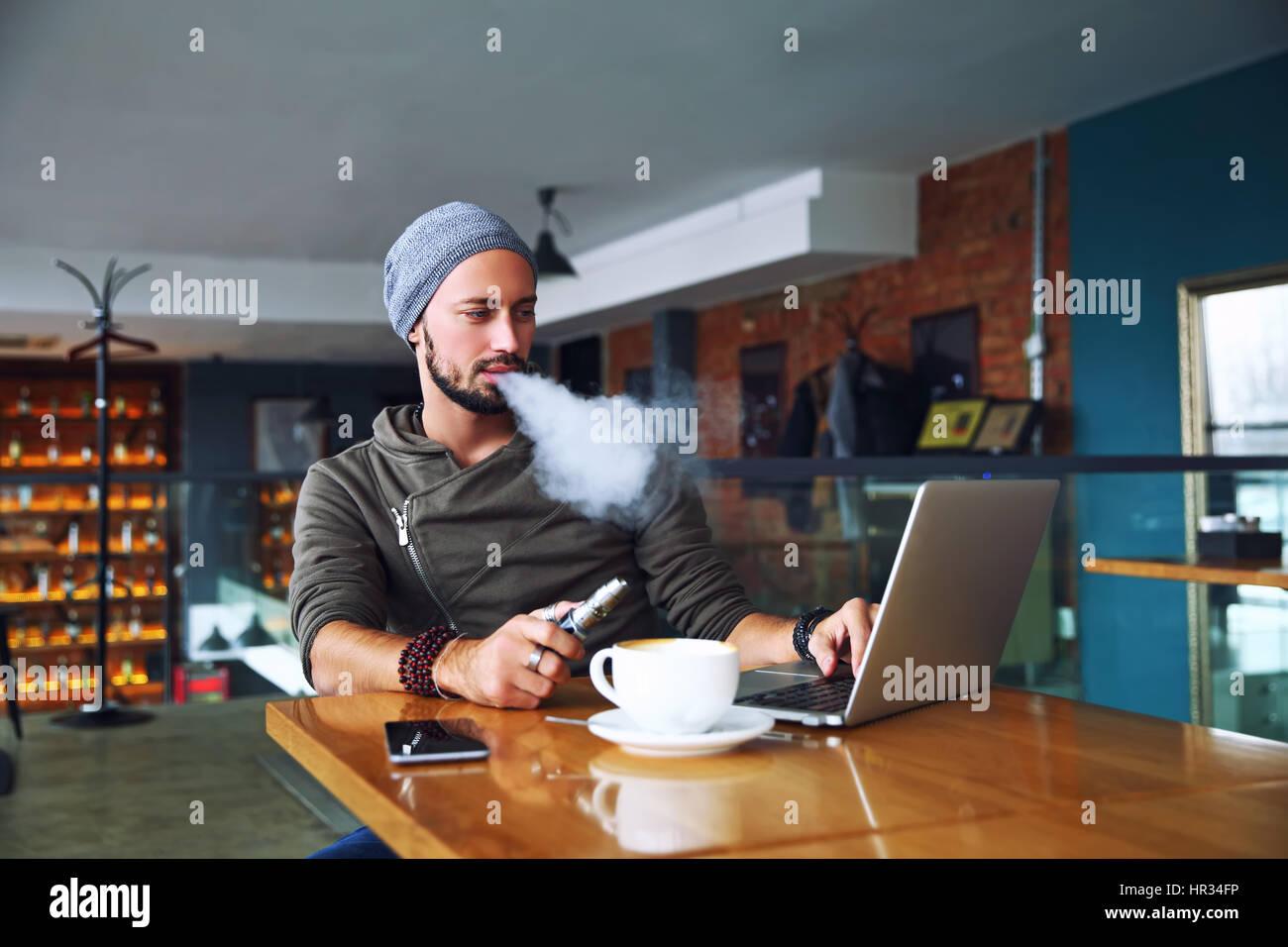 Junge hübsche Hipster Mann mit Bart sitzen im Café bei einer Tasse Kaffee, dampfen und Veröffentlichungen Stockbild