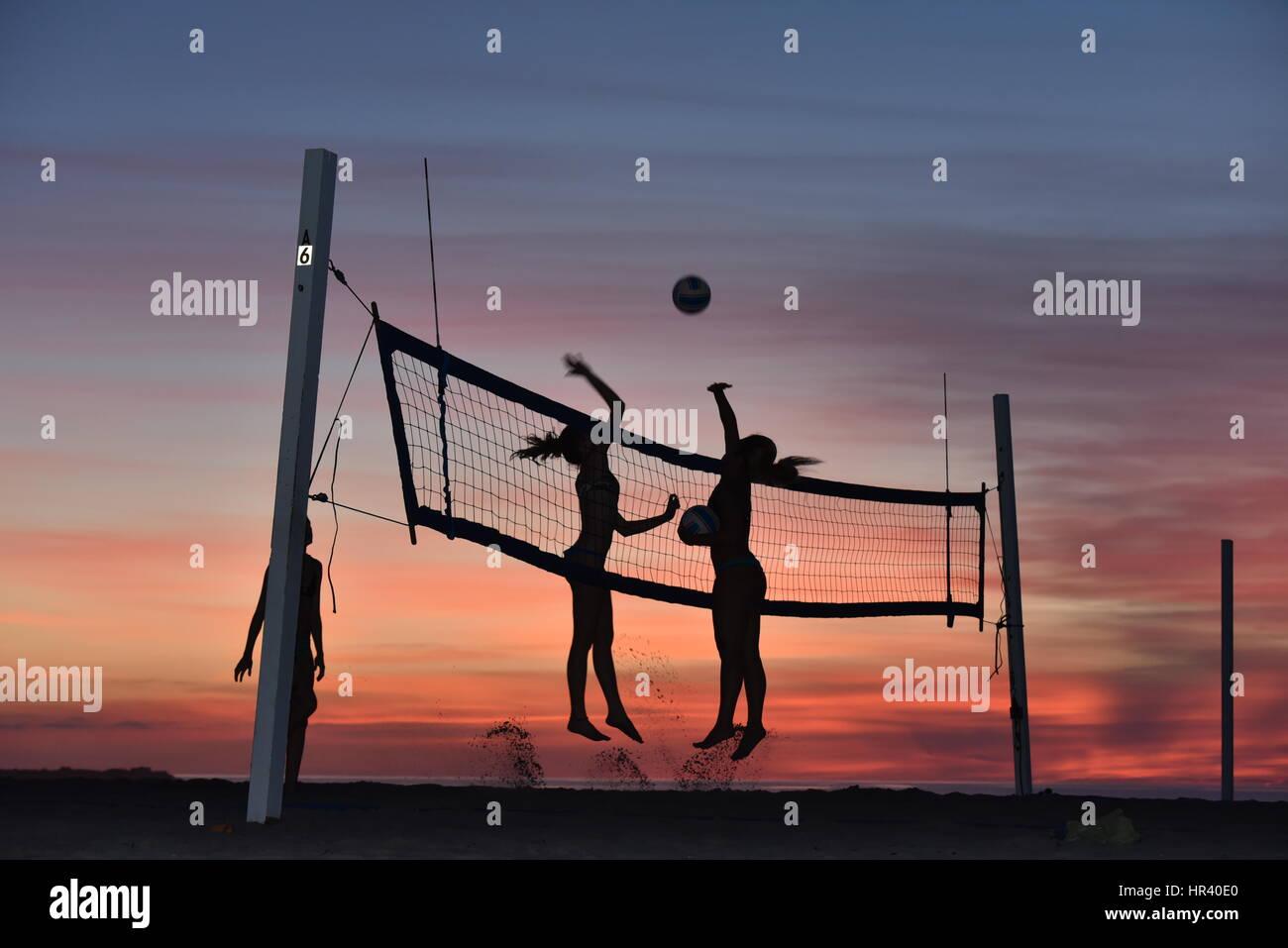 Silhouetten von weiblichen Volleyballspieler üben Volleyball am Strand bei Sonnenuntergang in Mission Beach, San Stockfoto