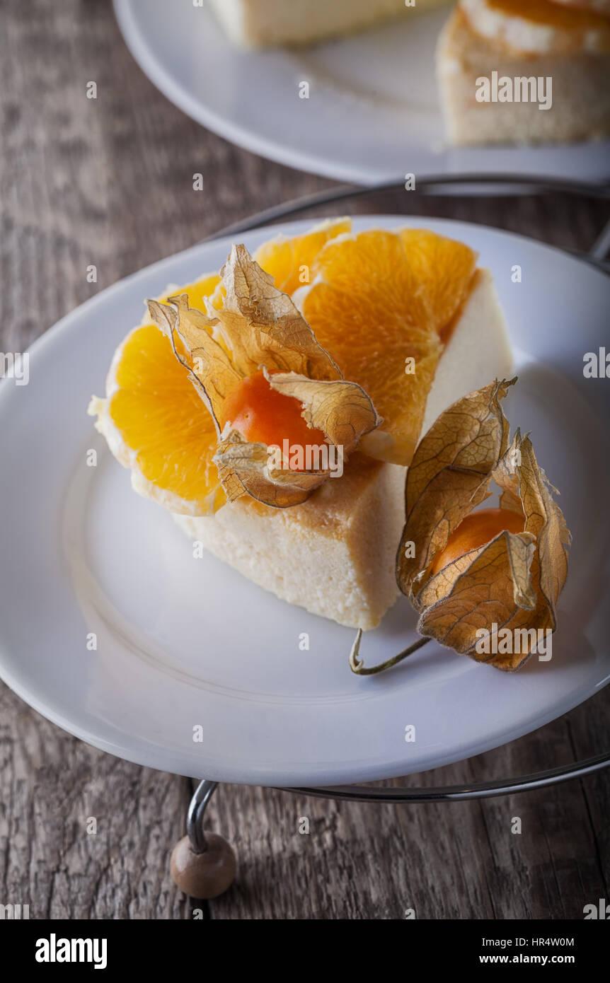 Käsekuchen mit Orangen und Physalis dekoriert Stockbild