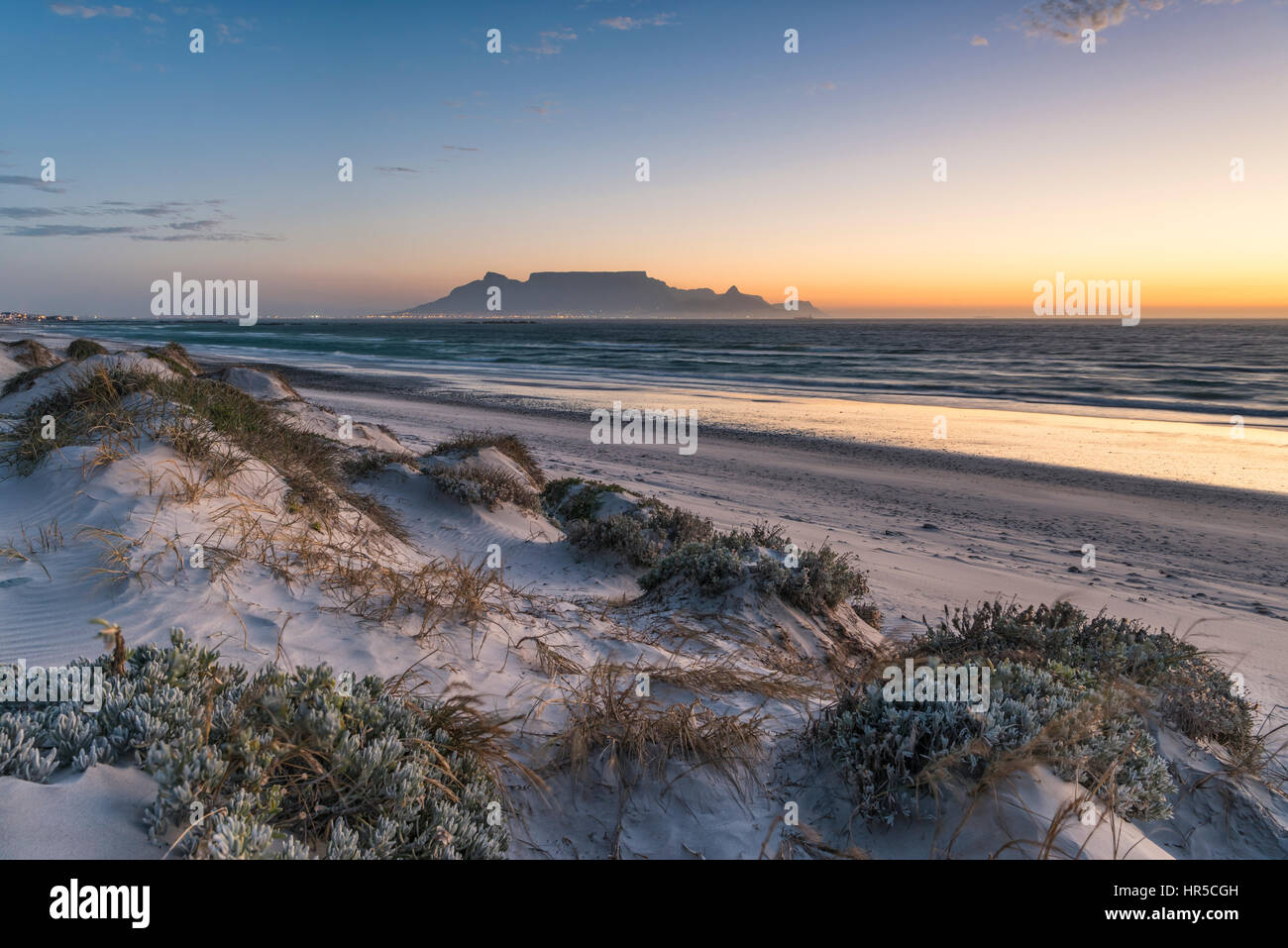 Blick auf den Tafelberg bei Sonnenuntergang von Big Bay Bloubergstrand, Kapstadt, Südafrika Stockbild