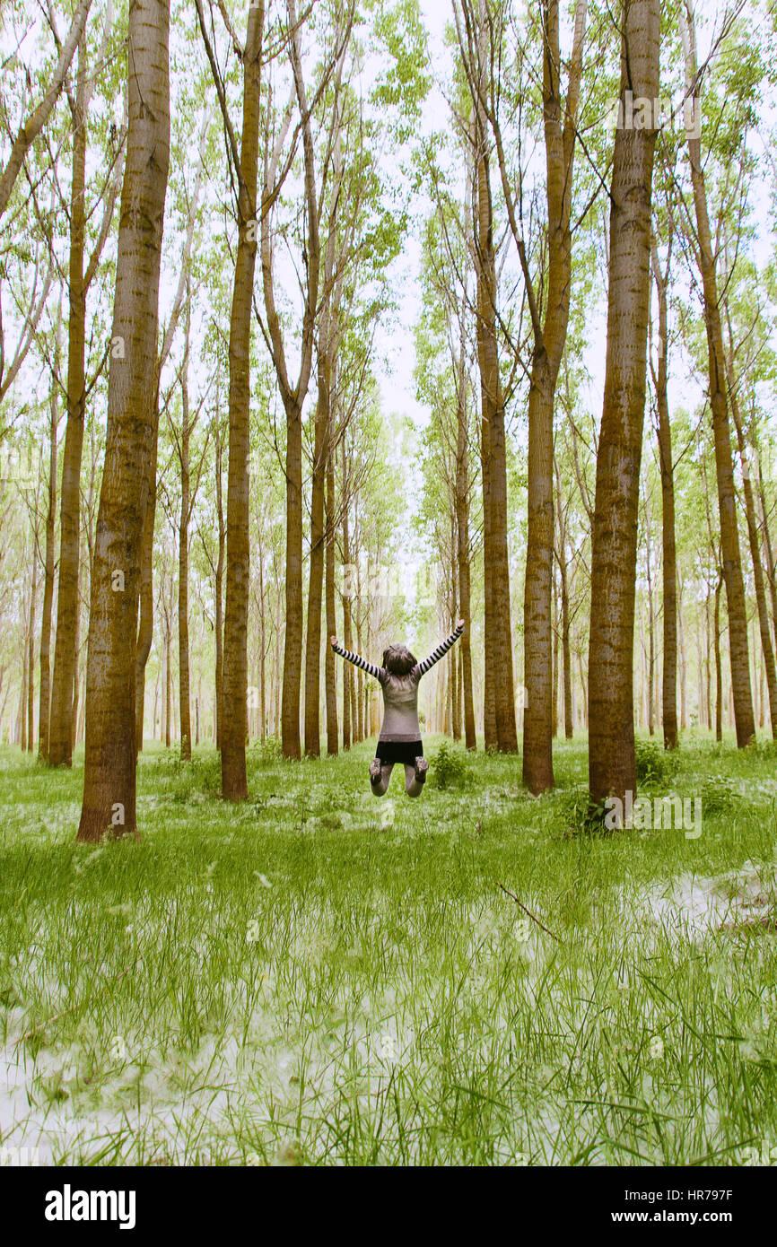 Kleine junge Frau, die zu Fuß durch einen Märchenwald Stockbild