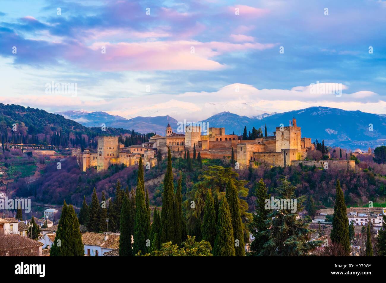 Alhambra-Palast bei Sonnenuntergang mit schneebedeckten Bergen der Sierra Nevada im Hintergrund. Granada, Andalusien, Stockbild