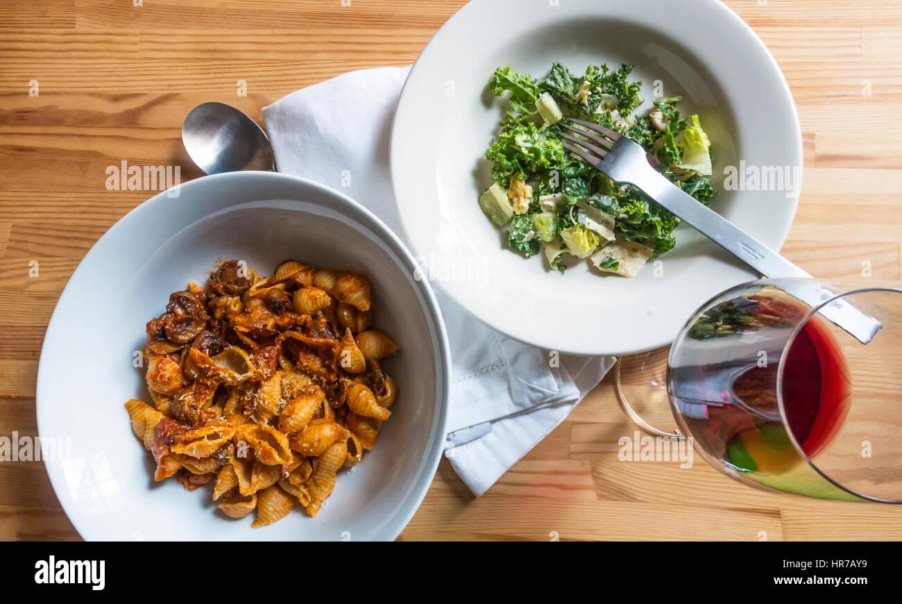 Nudeln Muscheln mit Speck, Champignons und Tomaten mit einem grünen Salat und Rotwein Stockbild