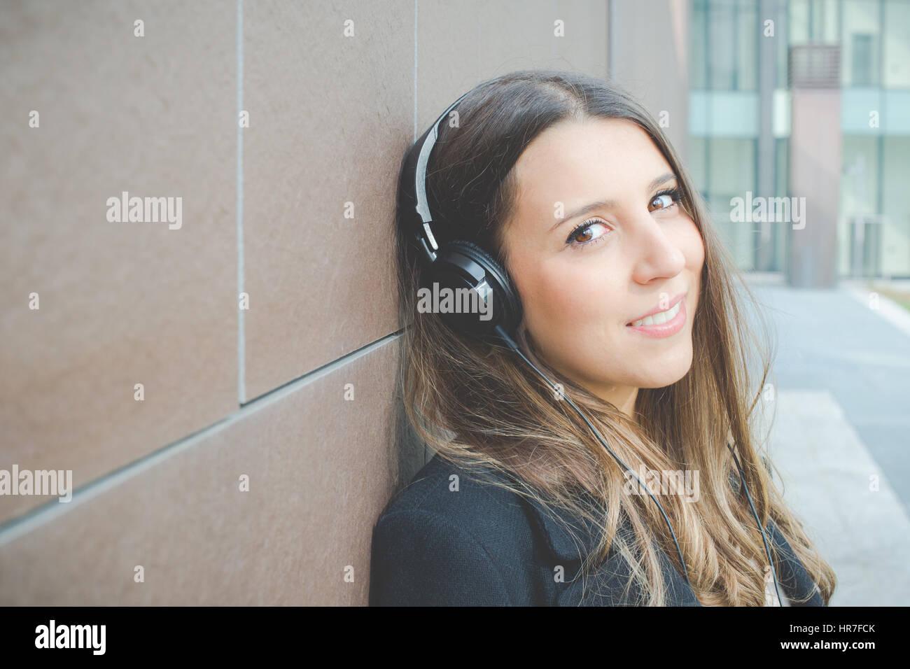 authentische junge Geschäftsfrau entspannt anhören von Musik in der Stadt Stockbild