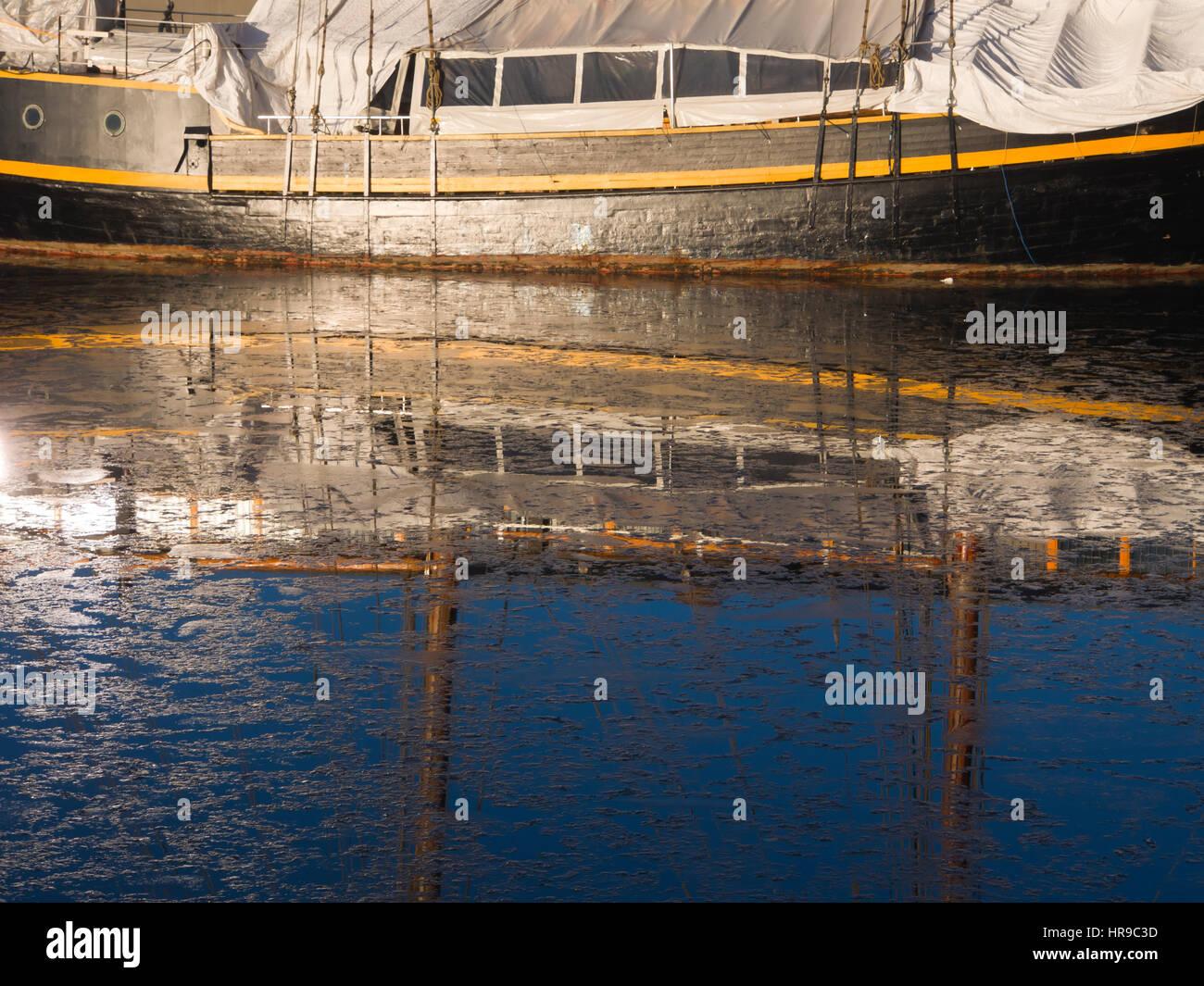 Segelschiff im Winterlager spiegelt sich in den eisigen Gewässern ...