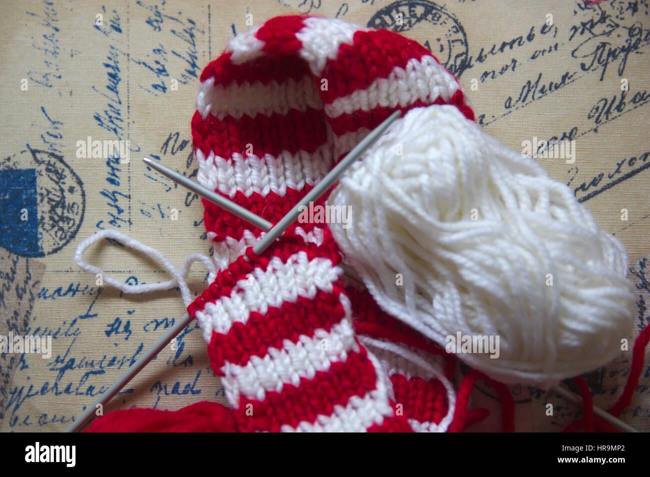 596dcb9f5d0bf9 Knäuel Wolle und Stricknadeln für machte einen roten und weißen Stockbild