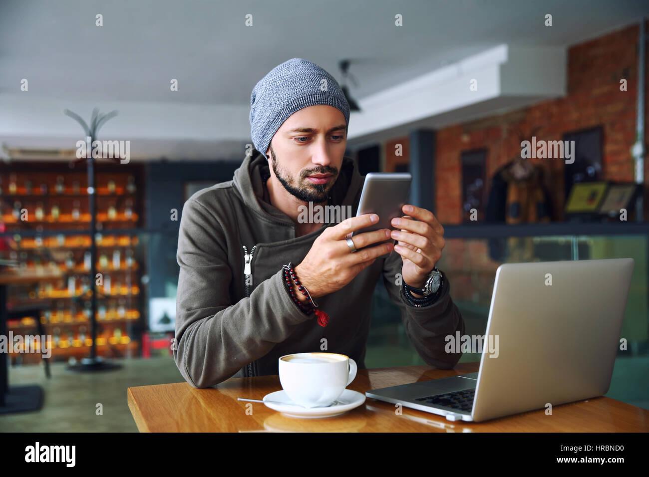 Fröhliche Hipster Mann an das Restaurant mit dem Handy telefonieren. Stockbild
