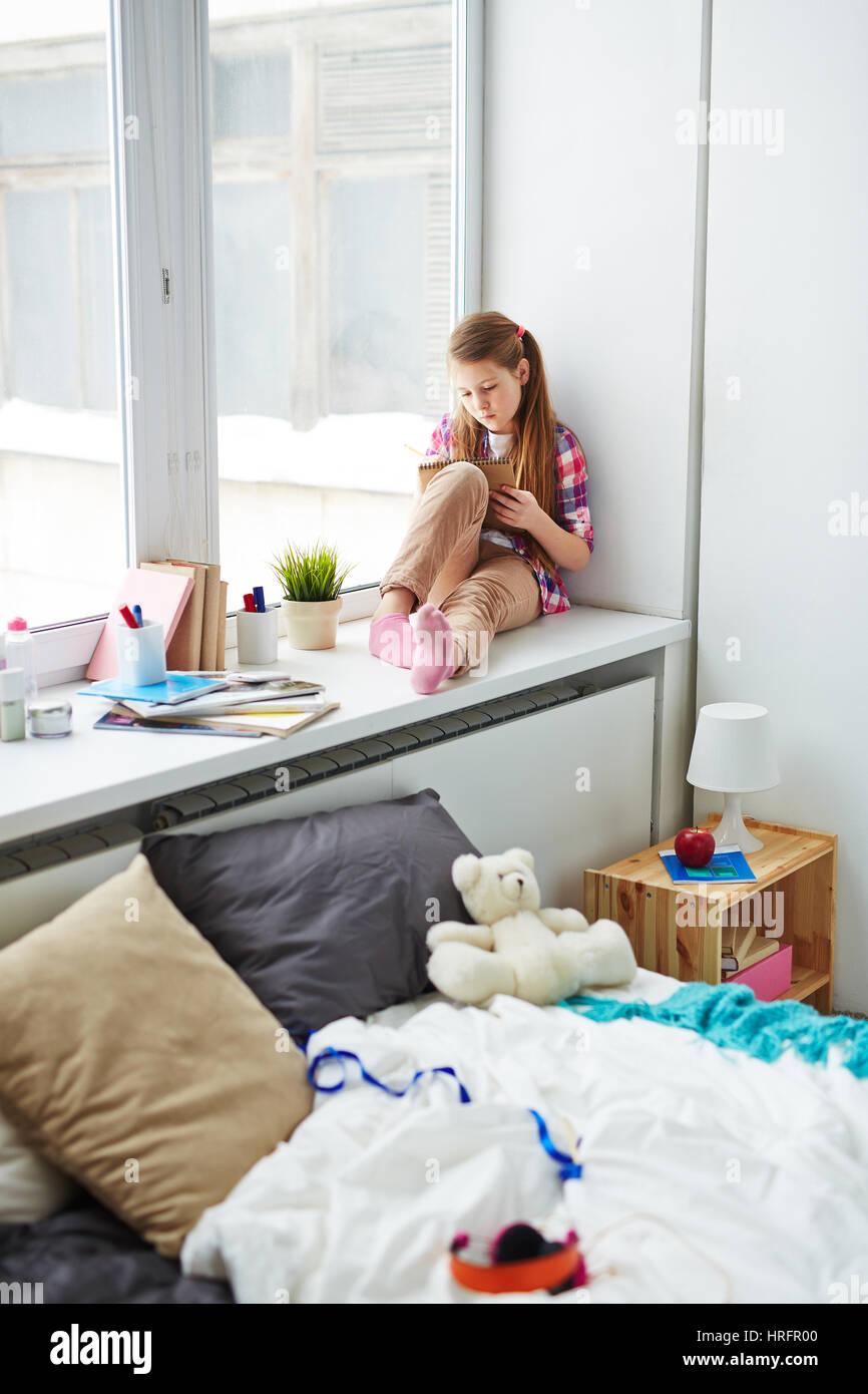Kleines Mädchen sitzt auf breite Fensterbank in ihrem gemütlichen ...