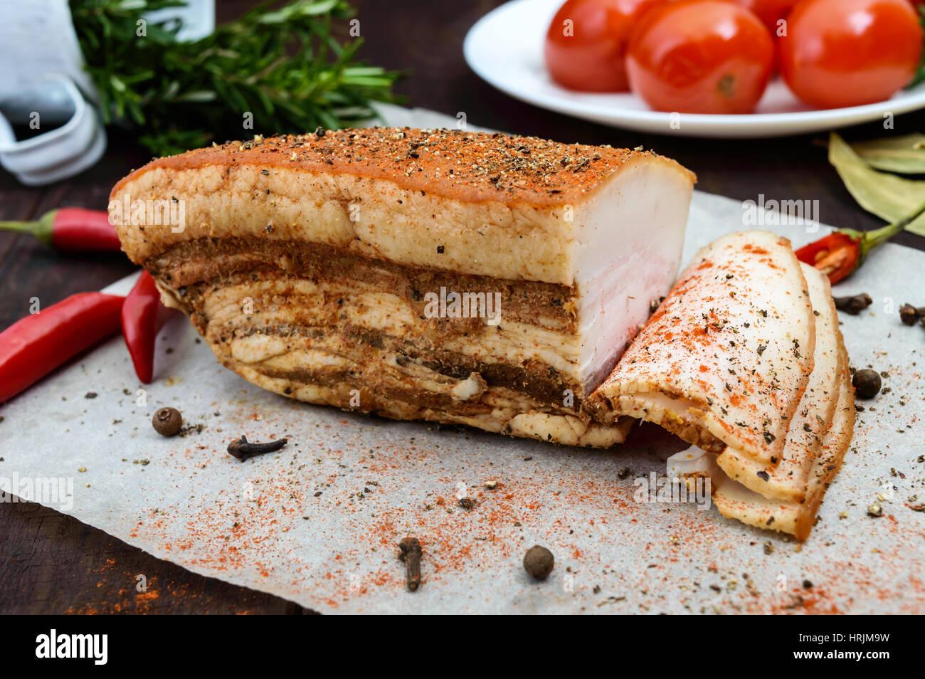 Ein großes Stück Speck gebacken mit Gewürzen und Kräutern auf einem Papier mit marinierten Tomaten. Stockbild