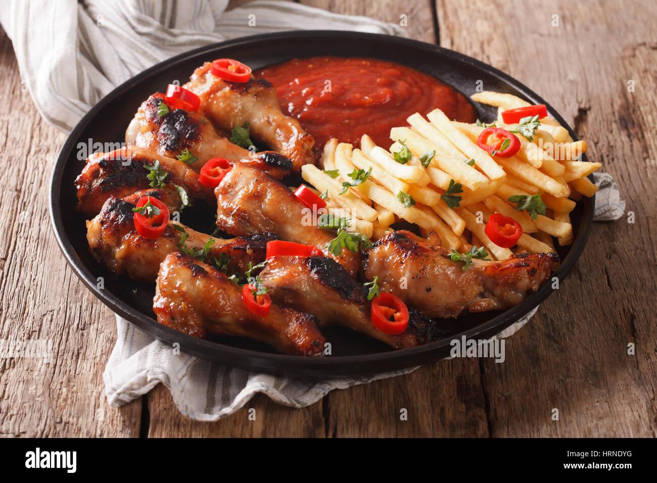 Servieren gebratene Hähnchenflügel mit Pommes Frites und Soße auf einer Platte Nahaufnahme. horizontale Stockbild