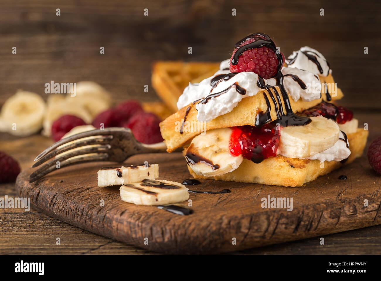 Belgische Waffeln mit Himbeeren, Bananen und Sahne auf rustikalen Tisch. Stockbild