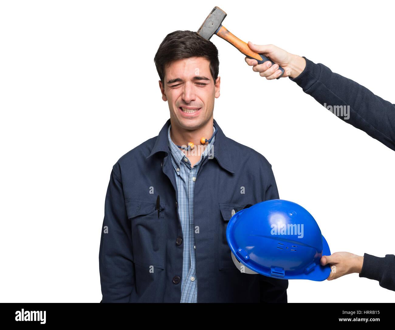 Arbeiter unter einem Hammerschlag auf den Kopf. Isoliert auf weiss Stockbild
