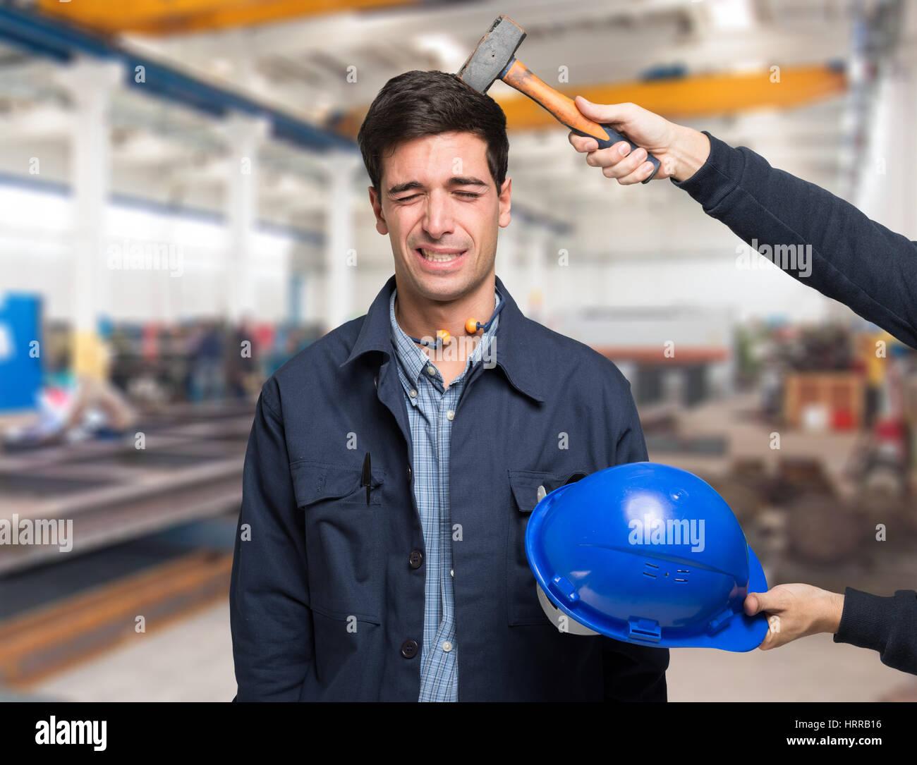 Arbeiter unter einem Hammerschlag auf den Kopf. Arbeit-Sicherheitskonzept Stockbild