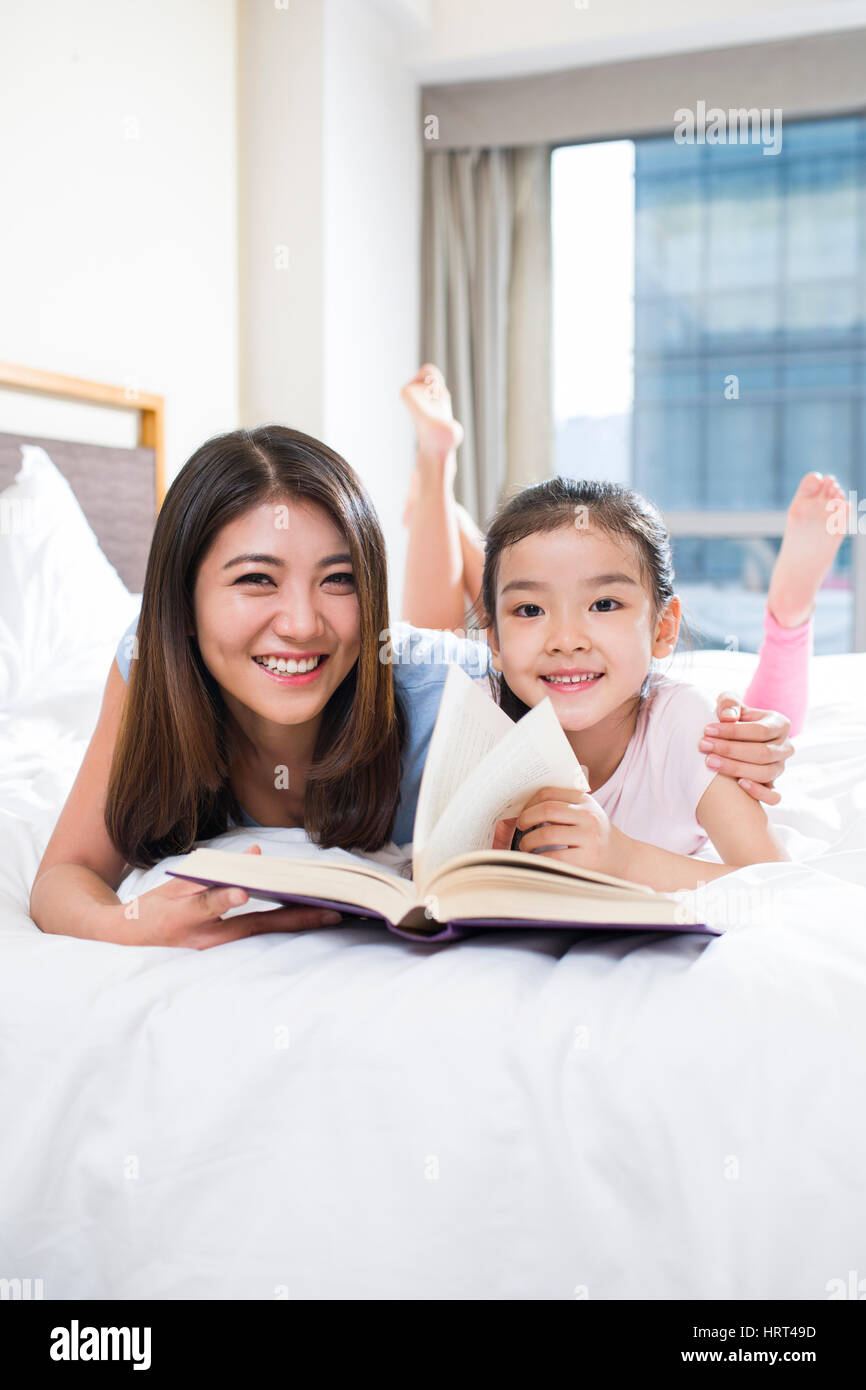 Kleines Mädchen, ein Buch zu lesen, mit Mutter Stockfoto