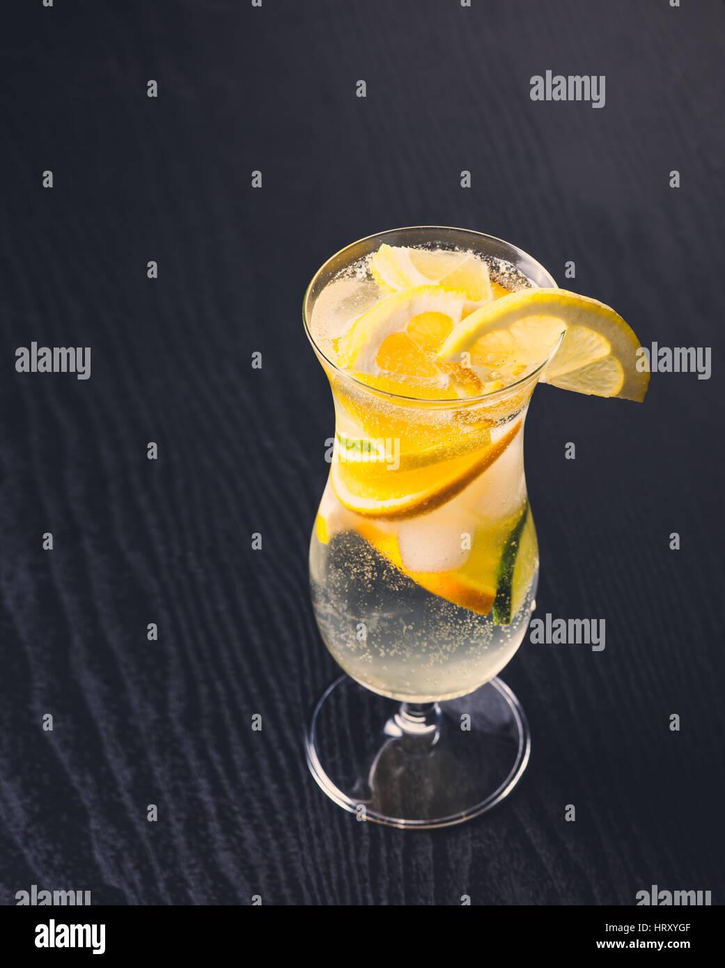 Frische alkoholisches Getränk mit Zitrusfrüchten auf dunklem Holz Stockbild
