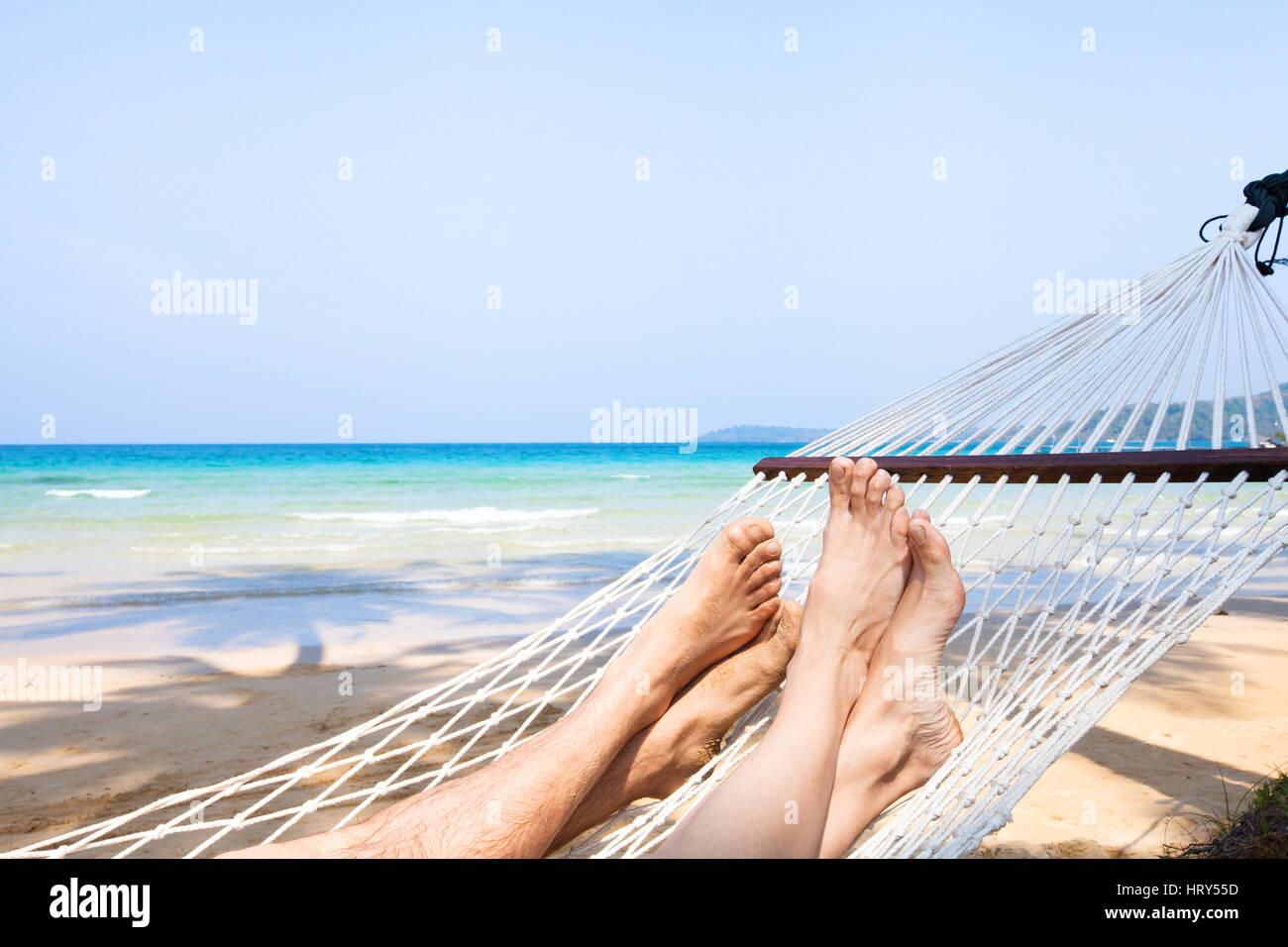 Urlaub mit der Familie am Strand, die Füße des Paares in der Hängematte, Entspannung Hintergrund Stockbild