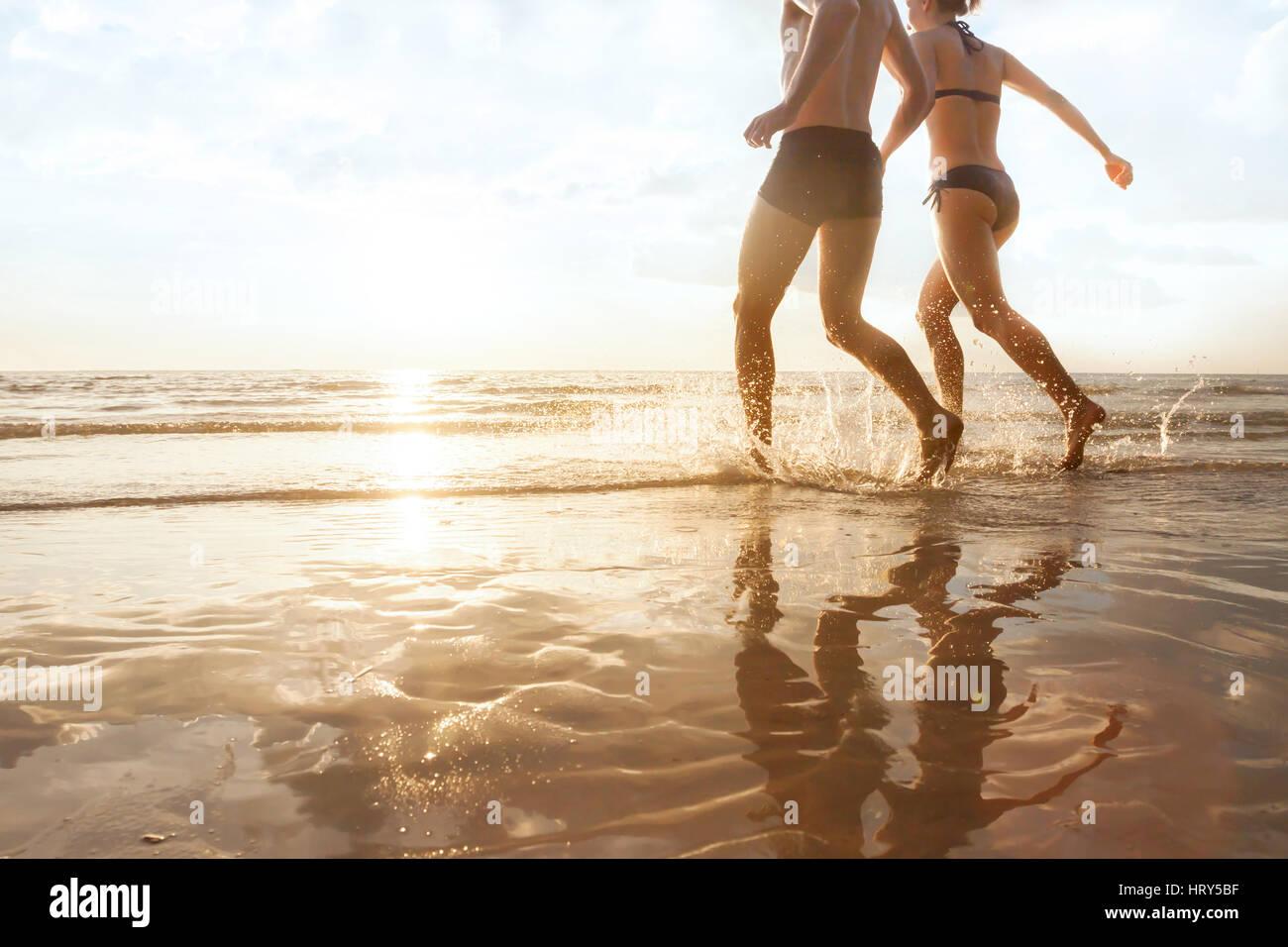 glückliches junges Paar läuft bis zum Meer am Strand bei Sonnenuntergang, Silhouetten von Mann und Frau, Stockbild
