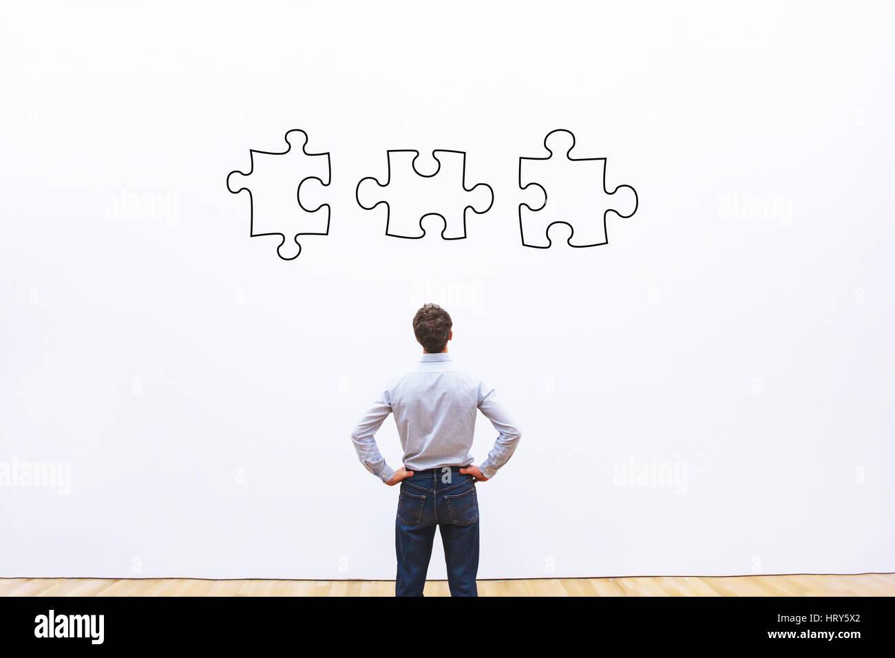 Business Solution-Konzept, Geschäftsmann, Blick auf die Teile des Puzzles Stockbild