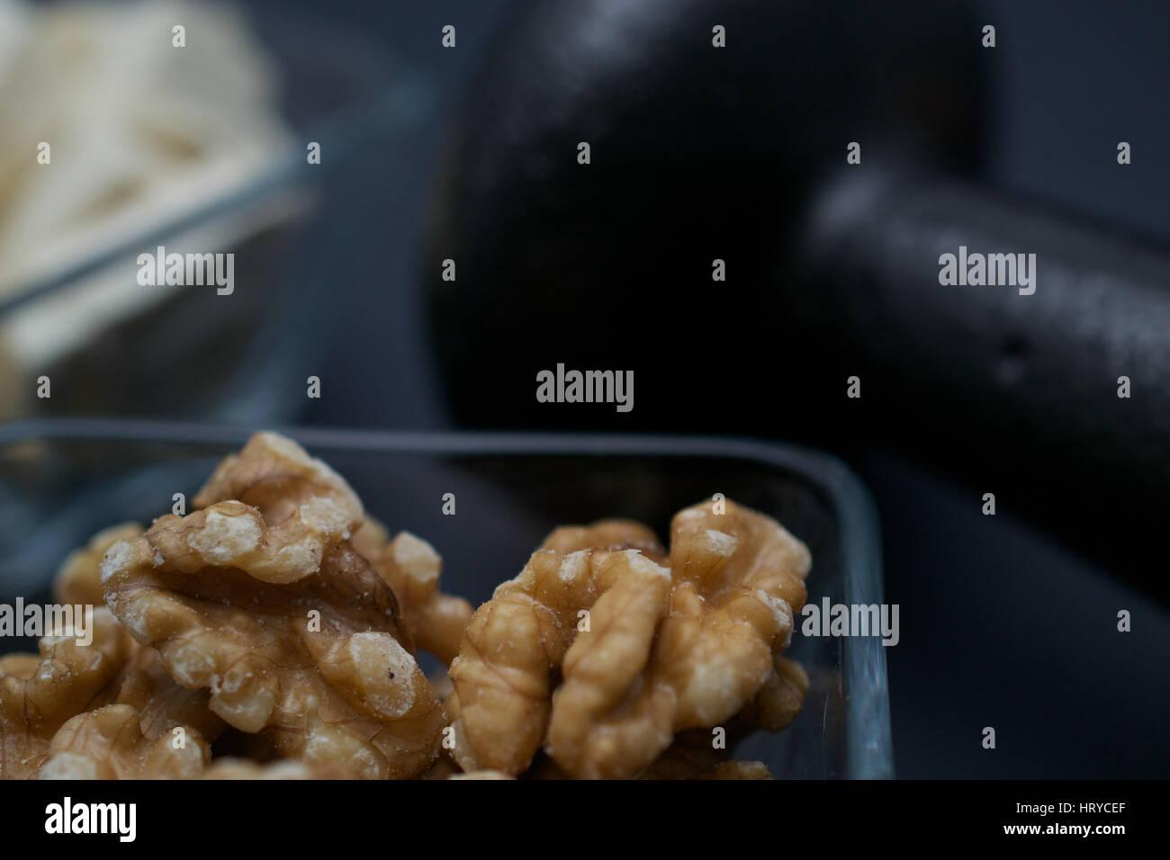 Closeup auf Hantel, Walnüsse und Tofu auf dunklem Hintergrund: Fitness und Gewicht-Verlust-Konzept. Stockbild