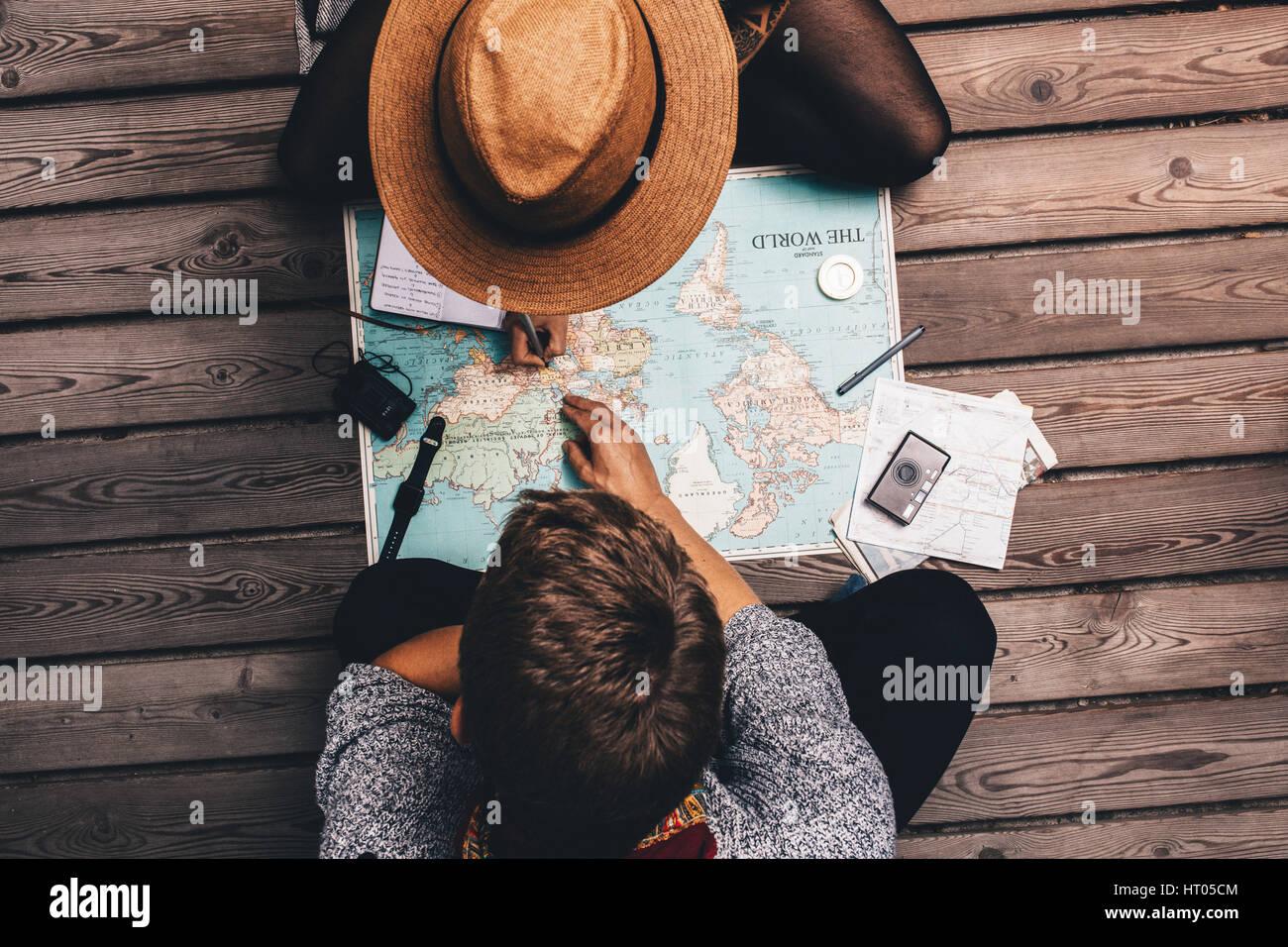 Mann und Frau Urlaub Pläne über die Weltkarte. Paar, sitzen die Karte und es zu erkunden. Stockbild