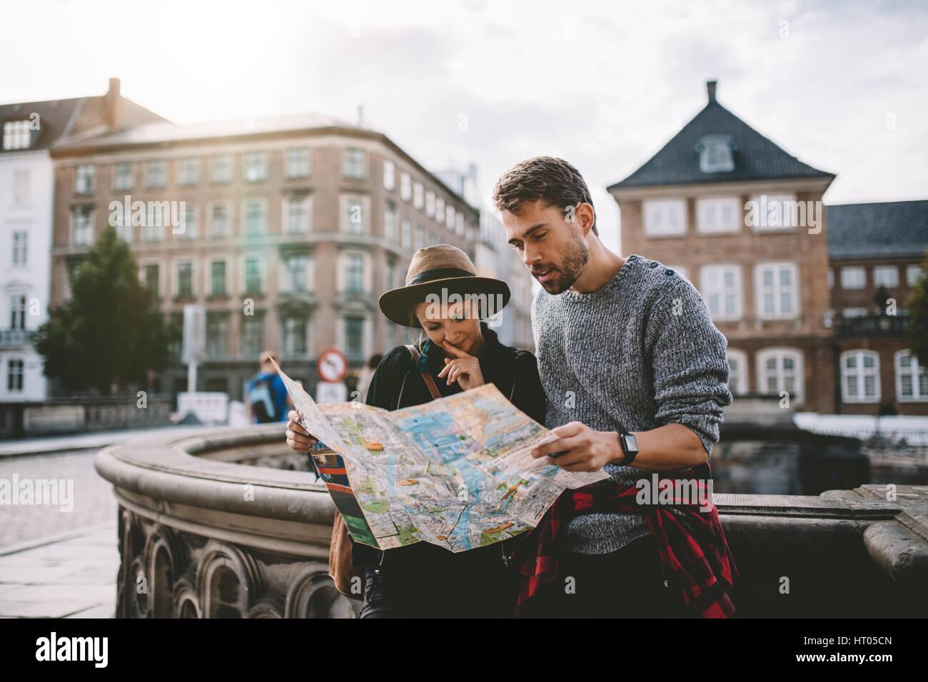 Junges Paar eine Navigationskarte der Stadt betrachten. Touristen finden ihren Weg auf einer Karte, die auf der Stockbild