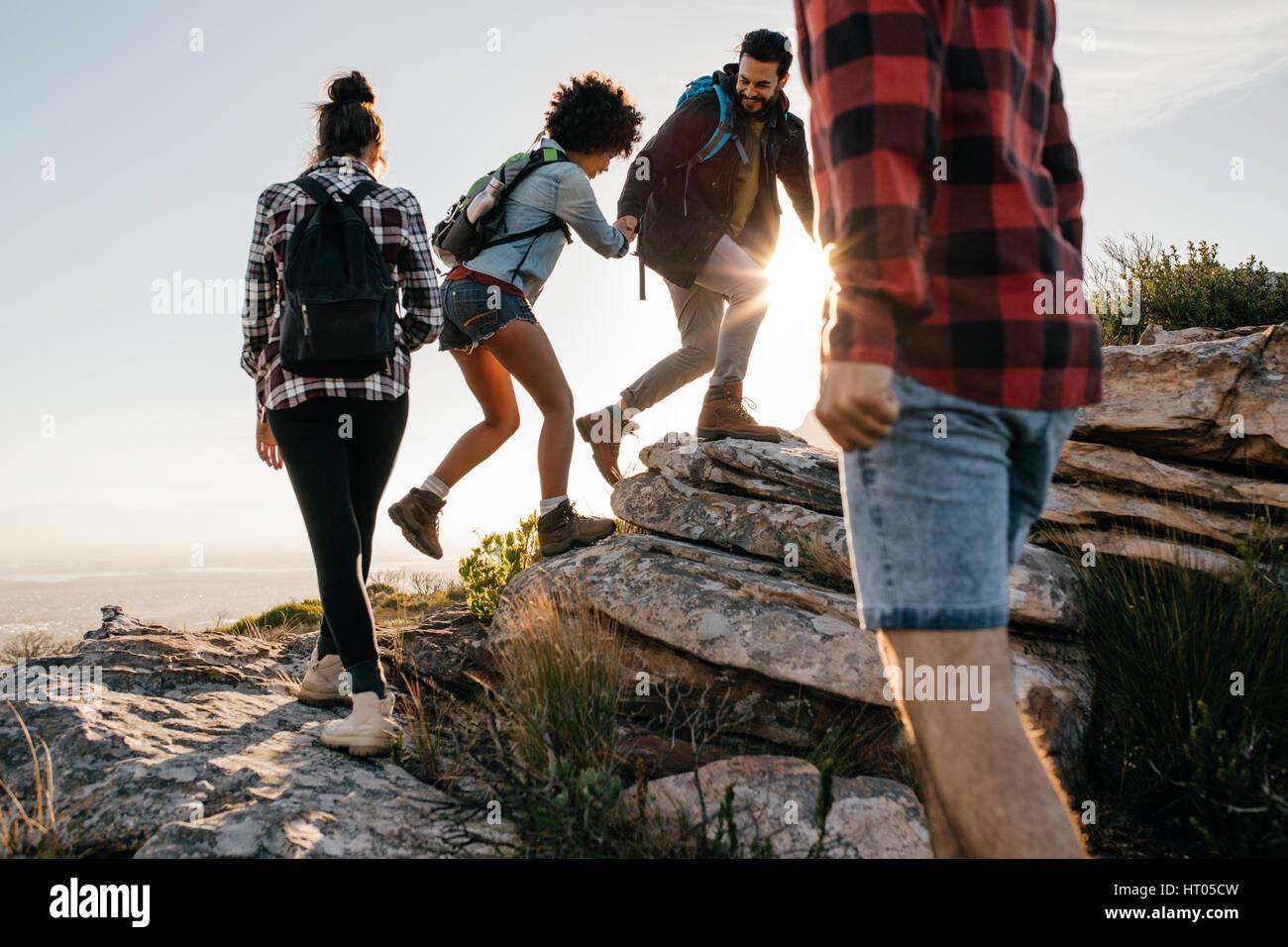 Gruppe von Wanderern mit Rucksäcken zu Fuß auf einem Berg. Vier Freunde machen einen Ausflug in die Natur. Stockbild